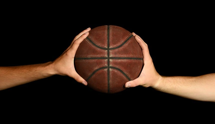 Two male hands palming a basketball